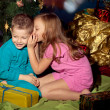 Little boy and girl near Christmas tree and gifts — Stock Photo #16870637