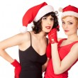 Two women wearing santa hats have fun — Stock Photo