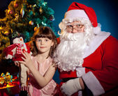 Santa Claus holding bag and little girl holding toy — Stock Photo