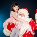 Santa holding girl on his shoulder — Stock Photo #17402137