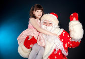 Santa holding girl on his shoulder — Stock Photo