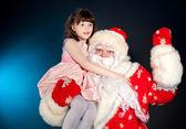 Santa holding girl on his shoulder — Stock Photo