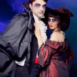 Man and woman wearing as vampire and witch. Carnival. fog. - Photo