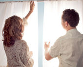 Man and woman hanging curtain — Foto de Stock