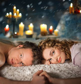 Sexy young couple lay in bed . Candles. — Stock Photo