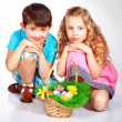 GIrl and boy wearing as Easter Rabbit sitting on the grass - Stock Photo