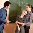 Portrait of a teacher explaining something to a smiling schoolbo — Stock Photo #24083075