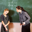 Portrait of a teacher explaining something to a smiling schoolbo — Stock Photo #24083089