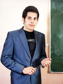 Confident young teacher and classic chalkboard background — Stock Photo