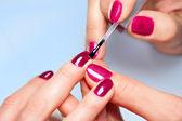 Woman applying nail varnish to finger nails  — Stock Photo