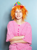 Funny girl wearing straped cloth,  red wig and  colorful hat — Stock Photo