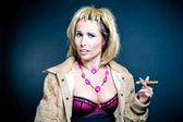 Prostitute smoking over dark background — Stock Photo