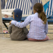Sibling sitting on the beach promenade — Stock Photo