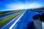 Motion blurred road and car — Stock Photo