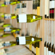 Wine shop, bottles on shelfs - Stok fotoğraf