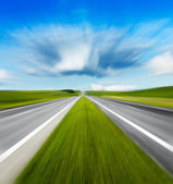 Motion blurred road and cloudy blue sky — Stock Photo