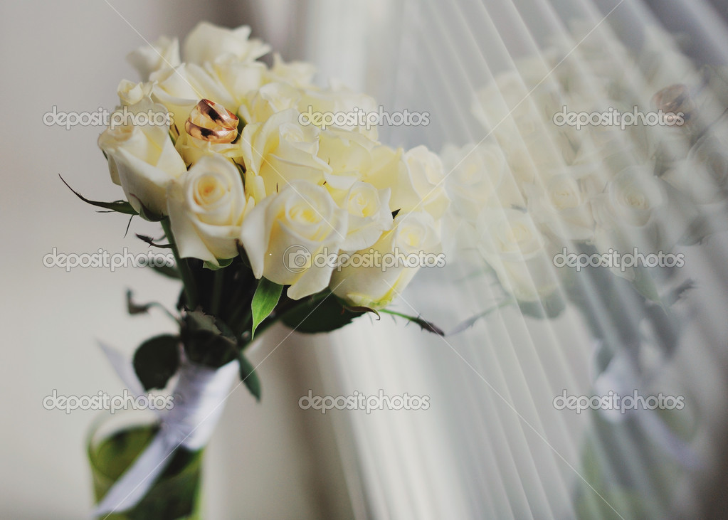 Wedding rings with white roses in the glass — Stock Photo #12603405