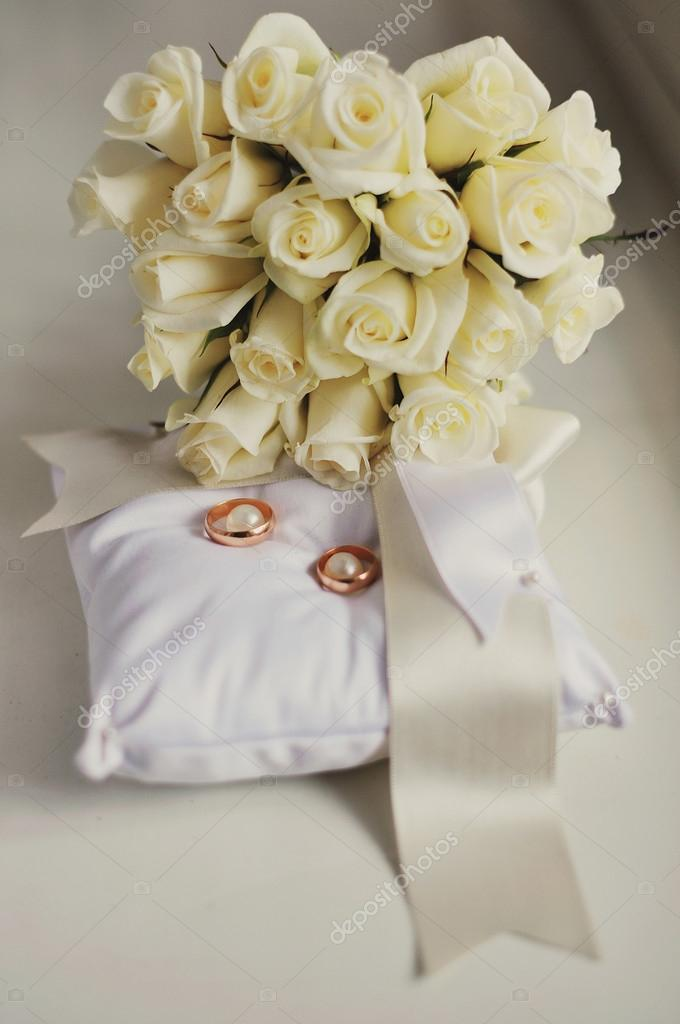 Wedding rings on a pillow and white roses — Stock Photo #12603419