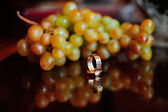 Wedding rings and grape — Stock Photo