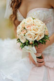 Bride holds a wedding bouquet of roses — Stock Photo
