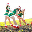 Three girls wearing santa claus clothes — Stock Photo