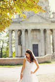 Beautiful bride stands next to old church — Stock Photo