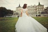 Gorgeous bride walking next to castle — Stock Photo