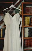 Hochzeitskleid in einem buchregal — Stockfoto