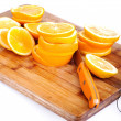 Foto Stock: Cut oranges on kitchen board