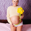 Beautiful young pregnant woman at home holding a daisy — Stock Photo