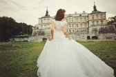 Gorgeous bride walking next to castle — Stockfoto