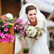 Smily bride next to flowers — Stock Photo #24221791