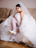 Beautiful Brunette bride getting dress her garter — Stock Photo