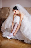 Brunette bride getting dress her garter — Stock Photo