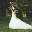 Gorgeous young brunette bride in forest — Stock Photo