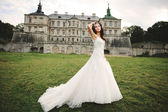 Brunette bride posing against castle in west Ukraine — Stock Photo