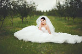 Beautiful young brunette bride posing in spring — Stock Photo