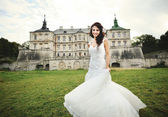 Young brunette bride against castle in west Ukraine — Stock Photo