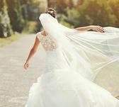 Gelukkig brunette bruid met sluier ronddraaien — Stockfoto