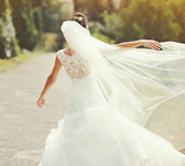 Happy brunette bride spinning around with veil — Stockfoto