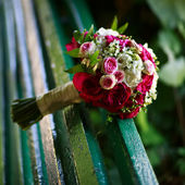 Bridal bouquet on a bench — Stock Photo