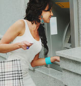 Cute woman gets cash from atm — Stock Photo