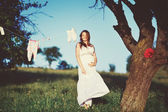 Pregnant woman in garden — Stock Photo