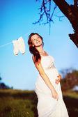 беременная женщина позирует в саду — Стоковое фото