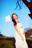 Pregnant woman posing in garden — Stock Photo
