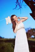 красивая беременная woma позирует в саду — Стоковое фото