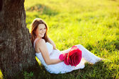 Beautiful pregnant woman with big red flower — Stock Photo