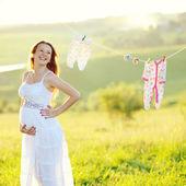 Junge schwangere frau in geschmückten garten — Stockfoto