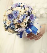 Young bride holding a wedding bouquet — Stok fotoğraf