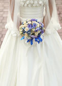 Caucasian bride holding a wedding bouquet — Stock Photo